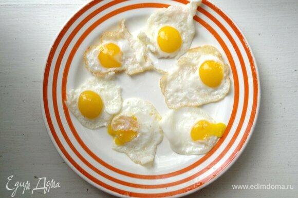 Выложить жареные яйца на тарелку и немного остудить.