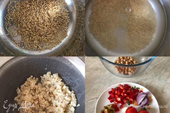 Булгур отварить до готовности в подсоленной воде, потом промыть и дать воде полностью стечь. Лук нарезать полукольцами, болгарский перец — кубиками, помидоры разрезать пополам, оливки — кружочками. Чеснок выдавить через пресс.