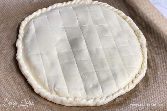 Оставшееся тесто также раскатать и накрыть им круг с ореховой начинкой. Хорошо скрепить края. Ножом сделать легкие насечки в виде узора сверху. Смазать поверхность яйцом. Выпекать 40–50 минут при 180°C до золотистого цвета. Если пирог быстро подрумянится, накройте его неплотно листом фольги.