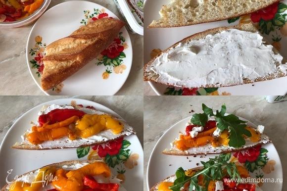 Теперь самое время приготовить бутерброды. Багет разрезать пополам и слегка поджарить в тостере. Потом смазать сливочным сыром и сверху разложить закуску из перцев.