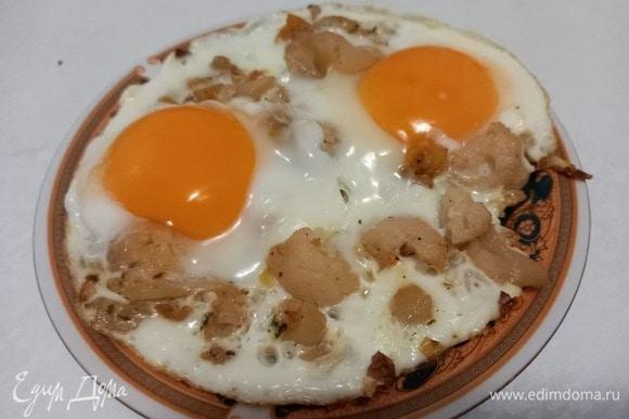 Поддевая яичницу лопаткой с краев, аккуратно, стараясь не повредить желток, перекладываем яичницу на тарелку.
