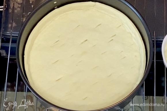 Достать тесто из холодильника, вырезать по форме дно и края высотой 3 см. Сначала уложите дно в форму, а затем — края, соедините по нижним бортам. Сделайте несколько проколов вилкой или ножом. Отправьте в духовку на 15 минут при 180°C