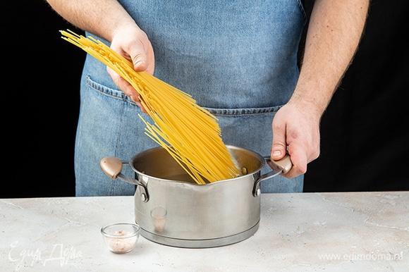 Отварите спагетти в подсоленной воде до состояния альденте. Воду слейте в отдельную емкость и сохраните. А спагетти верните в кастрюлю и накройте крышкой.