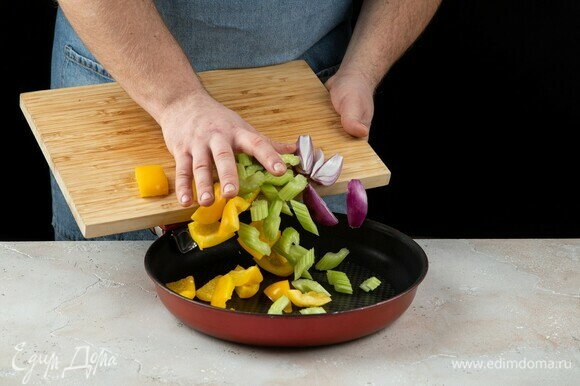 Перец, сельдерей и лук переложите в сковороду.