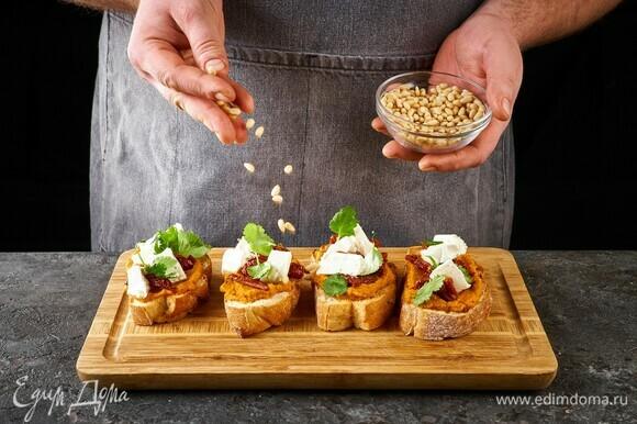Выложите на икру листья кинзы. Посыпьте кедровыми орешками.
