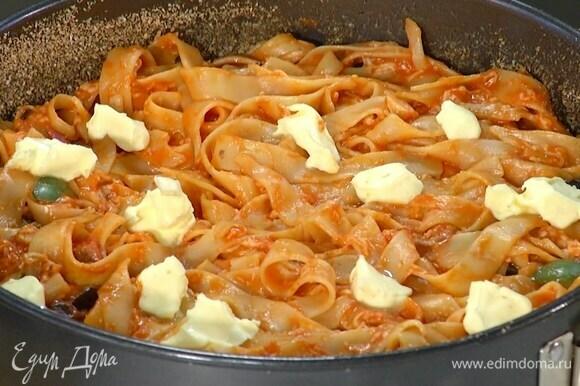 Выложить макароны с соусом в форму и равномерно распределить, сверху разложить маленькие кусочки оставшегося сливочного масла.