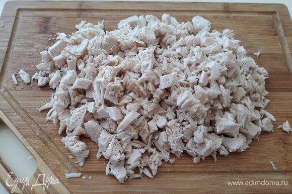 Отвариваем филе куриной грудки. Не забываем посолить во время варки. Нарезаем куриное филе кубиком. Выкладываем в салатник и смазываем майонезом.