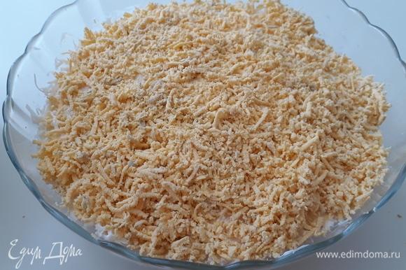 Верхним слоем натираем на мелкой терке яичные желтки и грецкие орехи. Салат готов!