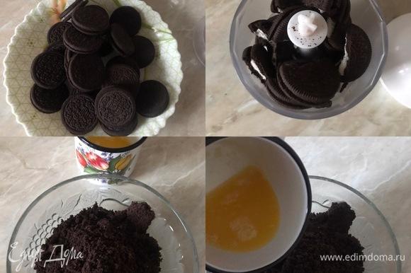 Духовку нагреть до 160°С. Сливочное масло растопить. В блендере измельчить печенье в очень мелкую крошку. Пересыпать крошку в миску, добавить растопленное масло и хорошо перемешать.