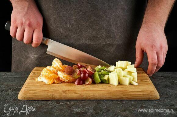 Яблоко и киви нарежьте кубиками. Ягоды винограда разрежьте на половинки, очистите от косточек. Мандарины почистите и разделите на дольки.