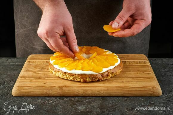 Соберите торт. Корж смажьте кремом, разложите персики.