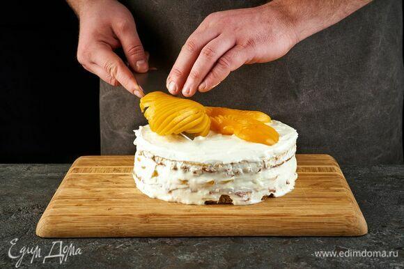 Накройте вторым коржом. Верх торта и бока смажьте кремом. Украсьте половинками персиков. Уберите в холодильник на 5–6 часов или на ночь.