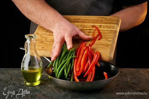 Добавьте в сковороду стручковую фасоль и болгарский перец, нарезанный соломкой. Обжаривайте примерно 2 минуты.