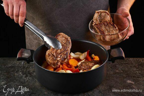 Верните в сковороду обжаренное мясо.
