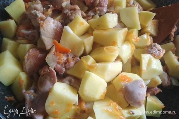 Очищенный и нарезанный картофель добавить к мясу и перемешать. Накрыть посуду крышкой и, не убавляя огня, парить жаркое в течение 20 минут, изредка помешивая.