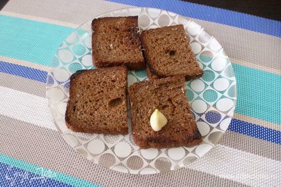 Натереть зубчиком чеснока подсушенную сторону хлеба.