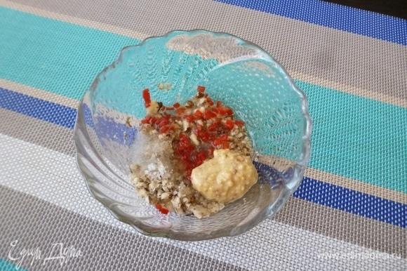 Приготовить заправку для салата. Грецкие орехи размять пестиком. Влить в миску растительное масло, положить горчицу и измельченный перец чили. Немного посолить (но помните, что в салате будут соленые огурцы).