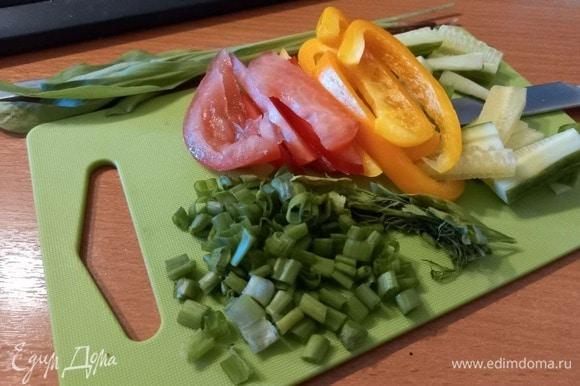 Огурцы режем небольшими брусочками, у томата удаляем жидкую часть (она размягчит лепешку) и режем вдоль небольшими слайсами. Перец чистим от сердцевины и режем небольшими полосками. Помидоры и перец лучше брать разных цветов (желтый и красный), так у нас будет вся цветовая гамма в тортилье. Укроп и петрушку отделяем от жестких веточек, зеленый лук мелко режем.