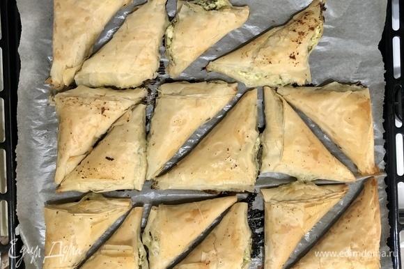Смазать пирожки сливочным маслом и выпекать в разогретой до 190°C духовке 20–25 минут.