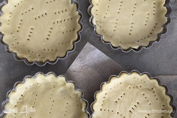 Охлажденное тесто разделить на 4 части, выложить тесто в формочки, прижать, наколоть вилкой по всей поверхности.