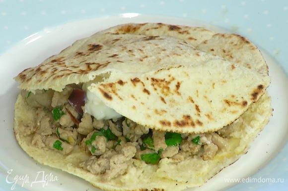 Питы прогреть с двух сторон на сухой сковороде, затем в каждой прорезать сбоку карман, внутрь поместить начинку и сметану, посыпать оставшейся кинзой.