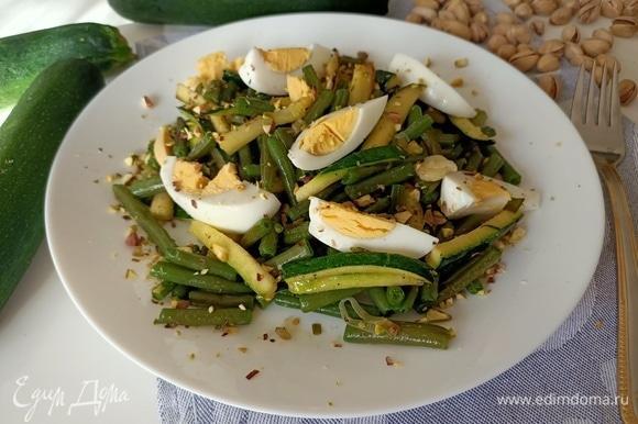 Убрать чеснок. Овощи выложить на блюдо, добавить куриные яйца и посыпать орехами. Салат готов. Его можно подавать как в холодном, так и в теплом виде. Фисташки можно заменить на кедровые орешки или миндаль. Приятного аппетита!