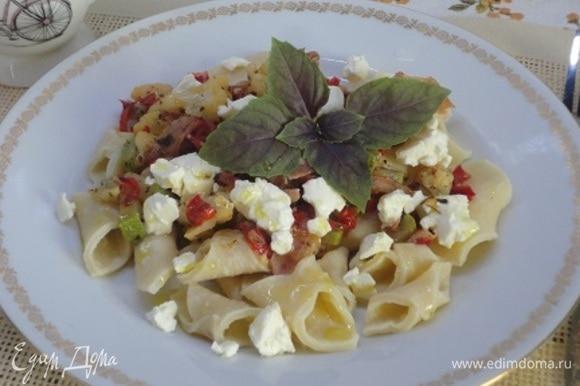 На тарелку выложить гаргарелли, сверху — овощи и кусочки рассольного сыра. Подавать со свежим базиликом.