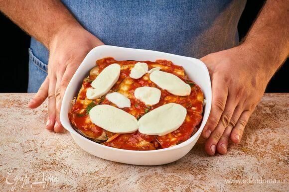 Выложите кусочки моцареллы и запекайте в заранее разогретой до 190°С духовке около 10 минут.