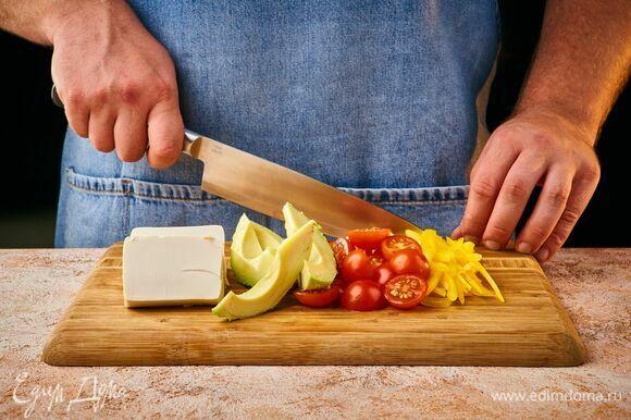 Нарежьте тофу крупными дольками. Помидоры черри — пополам, болгарский перец и авокадо — средними брусочками.