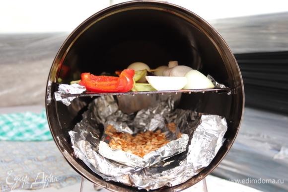 Коптилка у нас бочонком. Дно застелили фольгой для удобства. Щепу для копчения (у нас вишня) замочить в воде на 30–40 минут. На решетке разложить кусочки овощей в один слой. Поставить коптилку на «седые» угли и, когда из под крышки появится легкий дымок, коптить минут 15–25. Время зависит от желаемой степени копчения. Но дольше коптить не советую — овощи могут горчить.