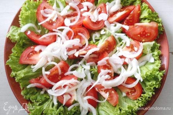 На листья салата выложить дольки помидоров. С лука слить жидкость и выложить лук на помидоры.