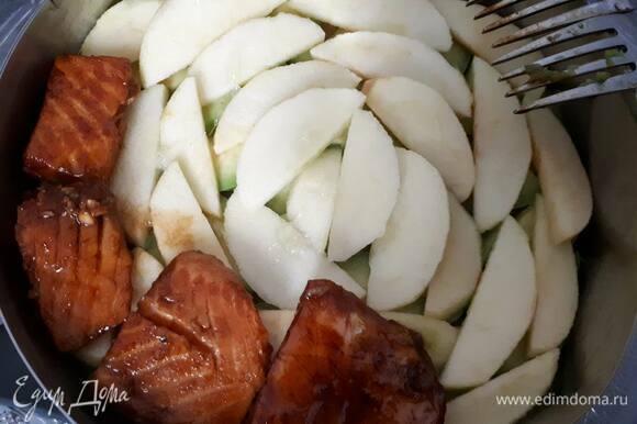 Выложите лосося на слой яблок. Толстые кусочки можно разрезать вдоль на две части.