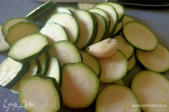 Цукини нарезать кольцами, чеснок раздавить тыльной стороной ножа. В глубокой сковороде разогреть оливковое масло, выложить цукини с чесноком и жарить в течение 2–3 минут.