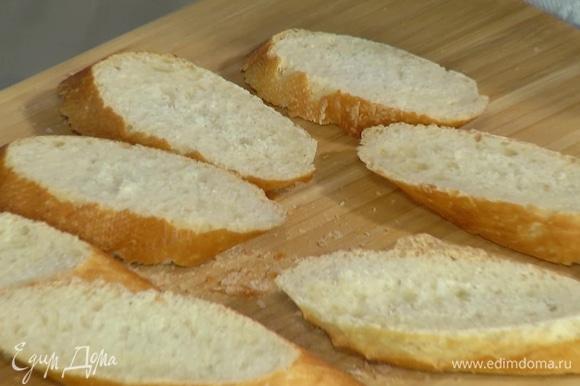 Багет нарезать кусочками и смазать с одной стороны сливочным маслом.