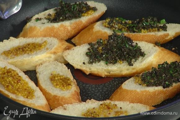 Разогреть большую сковороду и уложить хлеб маслом вниз, сверху смазать горчицей, выложить на каждый кусочек по 1 ч. ложке пасты из маслин.