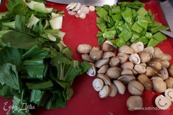 Нарежьте молодой горошек. Нарежьте соломенные грибы на половинки. У меня в рецепте кантонская капуста (или бок-чой). Можно использовать пекинскую капусту. В таком случае нужно взять половину кочана. У капусты отрежьте основание, удалите поврежденные листья, остальные листья крупно нарежьте.