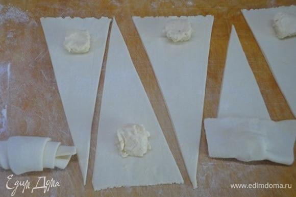 Готовое тесто размораживаем и раскатываем каждую часть в форму прямоугольника. Разрезаем на треугольники. Добавляем начинку в центр каждого по 1 ч. л. или по 1 кубику из формочек для льда. Защипываем начинку плотно, чтобы крем не вытек, и заворачиваем тесто. Выкладываем на противень.