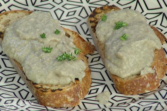 Хлеб нарезать и обжаривать на сухой сковороде-гриль с двух сторон до появления золотистых полосок, затем намазать паштетом и украсить оставшимися листьями тимьяна.