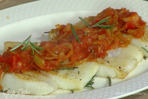 Готовую рыбу поместить на большую тарелку, сверху выложить соус, украсить оставшимися листьями розмарина.