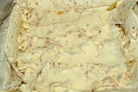 Выкладываем часть начинки. Сверху на начинку выкладываем смоченные в приготовленной смеси нарезанные кусочки лаваша. Кусочки хорошо смачиваем, выкладываем все. Закрываем одним пластом лаваша начинку и смоченный лаваш. Смазываем пласт кефирной смесью.