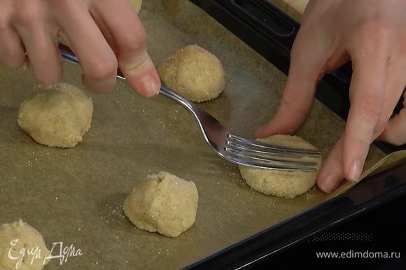 Из теста сделать шарики, обвалять в сахаре с корицей, выложить на застеленный бумагой для выпечки противень и придавить вилкой.