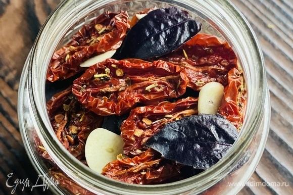 Готовые помидоры уложить в стерилизованные баночки (если хранение планируется длительное), чередуя их с тонкими дольками чеснока и листьями базилика.