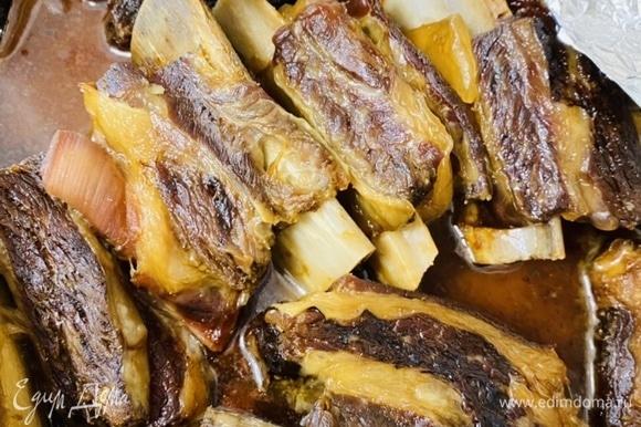 Достать ребрышки из духовки. Мясо должно легко отходить от костей и распадаться на волокна. Ребрышки переложить в другую емкость, а бульон, оставшийся от мяса, сцедить.