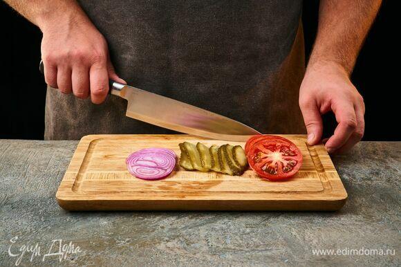 Нарежьте помидоры и лук кольцами, огурцы — тонкими пластинами.