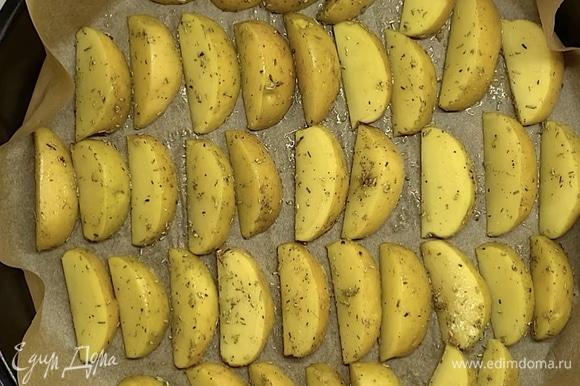 Выкладываем картофельные дольки на застеленный пергаментом противень. Ставим в заранее разогретую духовку на 20–25 минут при 180°C.