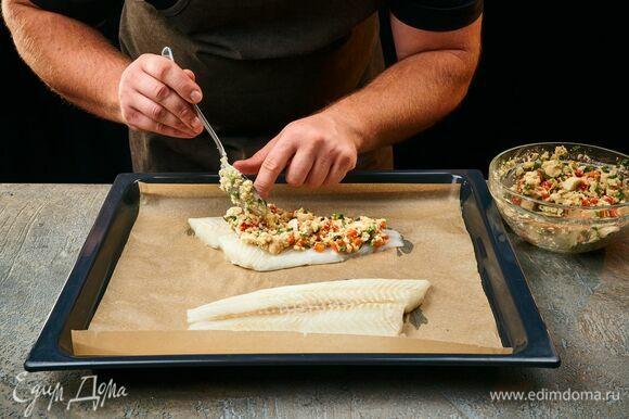 Рыбу обсушите, выложите на противень, застеленный пергаментной бумагой. Равномерно распределите грибную смесь по рыбному филе. Запекайте палтуса в предварительно разогретой духовке при 220°C около 8–10 минут.