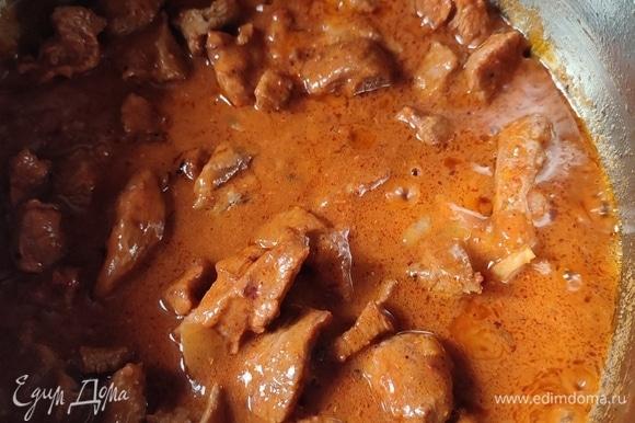 Вернуть мясо в кастрюлю к луку. Добавить паприку, лавровый лист и муку. Перемешать. Влить 200 мл воды, довести до кипения. Сделать огонь на минимум и тушить примерно 1 час под крышкой.