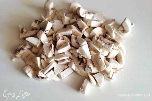 Грибы нарезать крупным кубиком. Растопить на сковороде сливочное масло, выложить грибы, немного обжарить, затем выдавить через пресс зубчик чеснока. Жарить грибы до испарения жидкости и золотистой корочки.