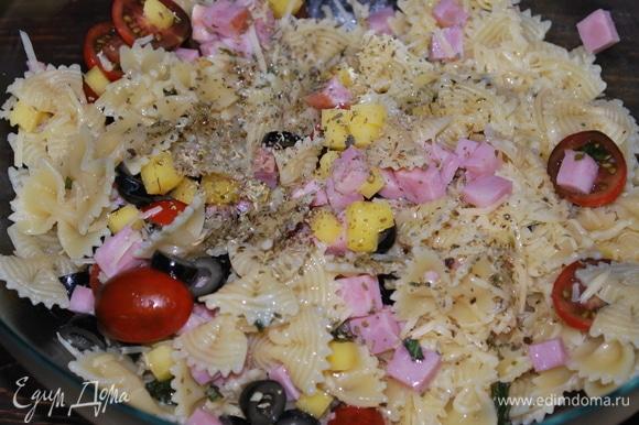В большой миске соедините ветчину, сыр, оливки. Готовую пасту откиньте на дуршлаг, чтобы стекла вода, и добавьте ее в миску. Свежий базилик мелко нарежьте, добавьте по вкусу свежемолотый черный перец, орегано и оливковое масло. Все перемешайте, отрегулируйте вкус с помощью трав и оливкового масла.