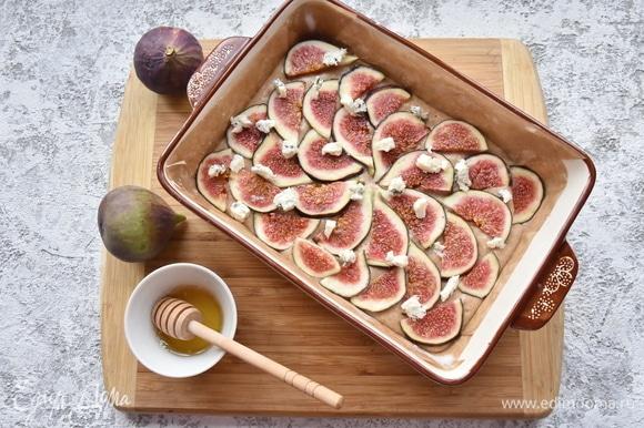 Инжир нарезать и выложить в произвольном порядке на тесто. Раскрошить сверху сыр и полить жидким медом. По желанию можно посыпать верх дробленым орехом. Выпекать в духовке, разогретой до 180°C, 40–45 минут. Готовность проверить лучинкой.